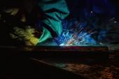 oříznutý obraz svářečka pájení kovu s jiskry v továrně