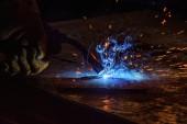 Fotografie oříznutý obraz svářečka pájení kovu s jiskry v továrně