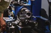 Fotografie ostřižená fotografie mužského výroba pracovníka v ochranné zástěry s nástrojem stroj v továrně