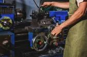 Fotografie částečný pohled mužského výroba pracovníka v ochranné zástěry s nástrojem stroj v továrně