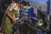 boční pohled na mužské výroba pracovníka v ochrannou zástěru a brýle s nástrojem stroj v továrně