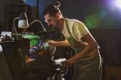 Koncentrovaná mužské výrobě dělník v ochrannou zástěru a brýle s nástrojem stroj v továrně