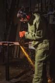 Fotografia lavoratore in googles protettivi di lavoro con la sega circolare nello stabilimento di produzione