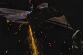 Fotografie oříznutý obraz dělník výroby pomocí kotoučové pily se leskne v továrně
