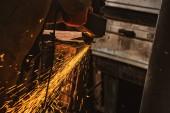 částečný pohled pracovníka pomocí kotoučová pila s jiskří v továrně
