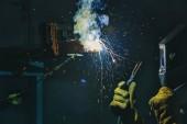 Stellen Sie Arbeiter Schweißen Metall mit Funken im Werk her