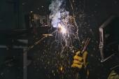 Fotografie boční pohled svářečka v ochranné masce pracující s kovem v továrně