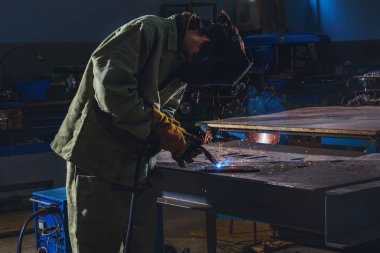 concentrated manufacture worker welding metal with sparks at factory