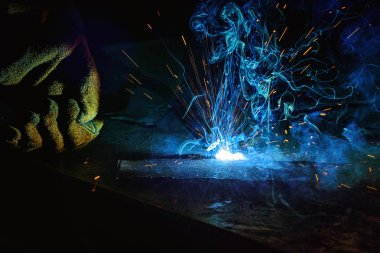partial view of worker welding metal with sparks at factory