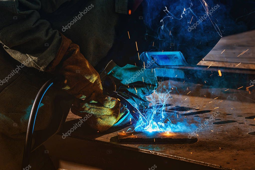 Partial view of welder in protection mask brazing metal at factory stock vector