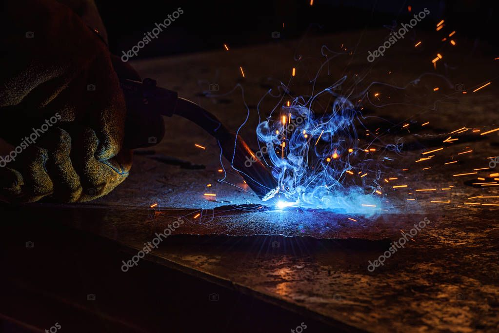 Cropped image of welder brazing metal with sparks at factory stock vector