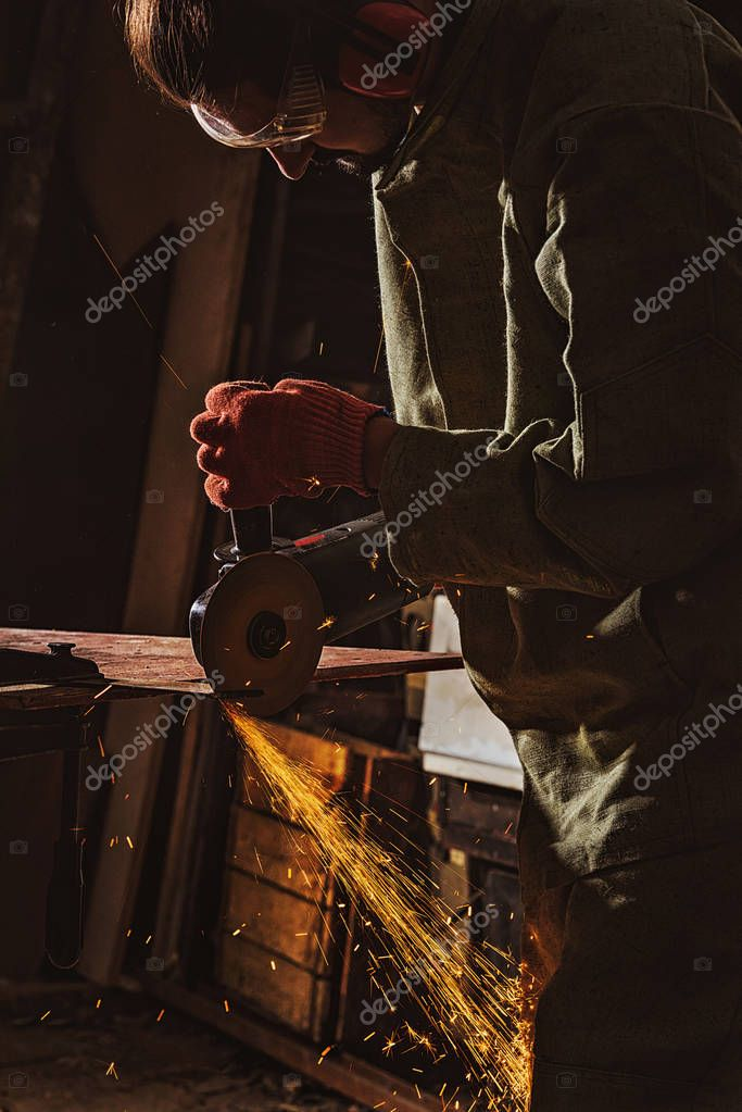 Focused male worker in protective googles working with circular saw at factory stock vector