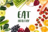 Fotografie pohled shora ujednání s čerstvou zeleninu, ovoce a bobule, izolované na bílém s nápisem jíst zdravě