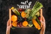 partial view of woman holding wooden box with healthy vegetables, fruits and detox drinks with eat green lettering