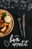 Fotografie pohled shora na pečené brambory s omáčkou na dřevěném prkénku a vidlice s nožem na černém pozadí s nápisem dobrou chuť