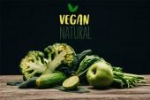Fotografie zblízka pohled čerstvé zdravé zeleniny a ovoce na dřevěný povrch na černém pozadí s nápisem Veganská přírodní