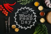 Fotografie top view of various sauces, grilled garlic, fork with knife and fresh vegetables with herbs on black background with world food day lettering