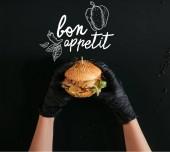 oříznuté záběr rukou v rukavicích drží vynikající burger s Tureckem, zeleninou a dresinkem na černém pozadí s nápisem dobrou chuť