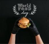 Fotografie oříznuté záběr rukou v rukavicích drží vynikající burger s Tureckem, zeleninou a dresinkem na černém pozadí s nápisem Světový den potravin