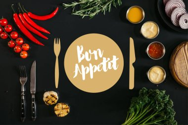 Top view of various sauces, grilled garlic, fork with knife and fresh vegetables with herbs on black background with