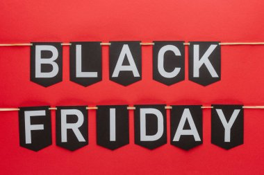 black friday lettering on flag garlands in lines isolated on red
