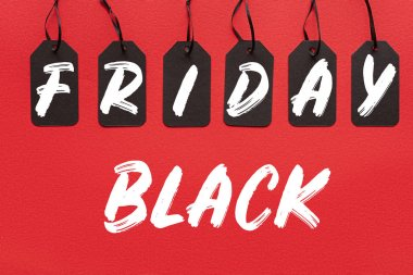 black sale tags isolated on red with black friday lettering
