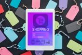 Fotografia vista superiore della tavoletta digitale con shopping app sullo schermo che si trova sul tag variopinte di vendita