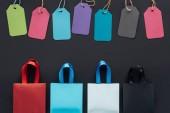 Fotografia vista superiore di sacchetti della spesa variopinti e vendita tag su sfondo nero per nero venerdì