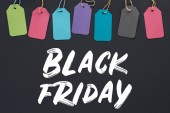 top view of colorful sale tags on black background with black friday lettering