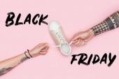 abgeschnittene Ansicht tätowierter Kunden, die Schnürsenkel von Turnschuhen isoliert auf rosa mit schwarzem Freitagsschild ziehen