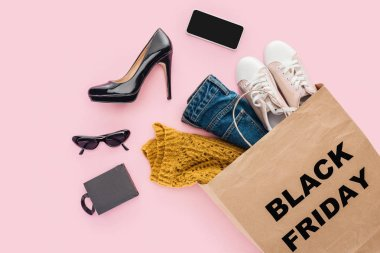 flat lay with clothes in shopping bag with black friday sign isolated on pink