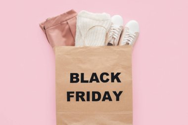 top view of stylish clothes in shopping bag with black friday sign isolated on pink