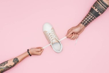 cropped view of tattooed shopaholics pulling sneaker isolated on pink