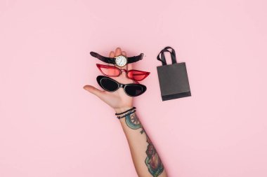 cropped view of tattooed woman holding trendy sunglasses and watch near little shopping bag isolated on pink