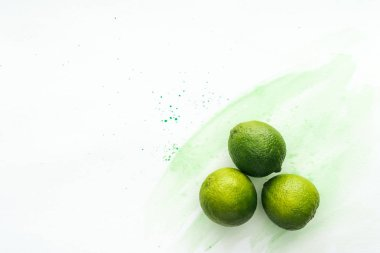 top view of three ripe limes on white surface with green watercolor