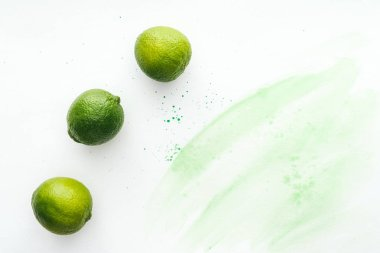 elevated view of three ripe limes on white surface with green watercolor