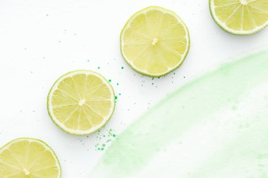 top view of pieces of ripe bright limes on white surface with green watercolor