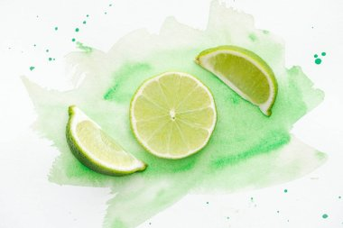 top view of pieces of green ripe limes on white surface with green watercolor