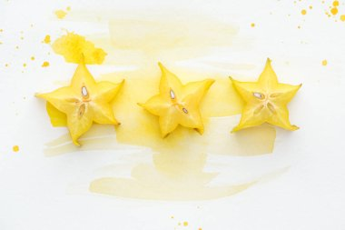 Top view of star fruits in row on white surface with yellow watercolor stock vector