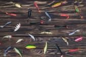 Fotografie pohled uspořádány různé rybářské návnady na dřevěné pozadí