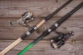 pohled shora na rybářské pruty na dřevěné pozadí, minimalistické pojetí