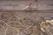 elevated view of fishing net and fishing float on wooden background
