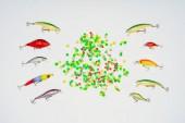 pohled shora barevné bonbóny, obklopen rybářské návnady umístěné v řádcích izolované na bílém