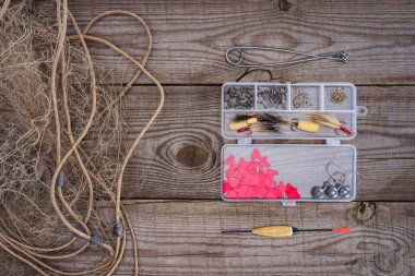 elevated view of fishing net and plastic box with fishing tackle and hooks on wooden background