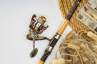 top view of fishing rod, nautical rope and plastic box with fishing tackle and bait isolated on white