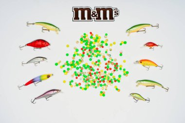 Elevated view of colorful candies surrounded by fishing bait placed in rows and sign m&m's isolated on white stock vector