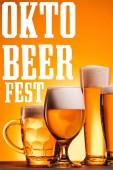 rendezett bögre hideg sör bevezetésekor a narancssárga háttérrel, az oktoberfest felirat