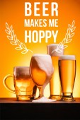 Fotografie arranged mugs of cold beer with froth on orange background with beer makes me hoppy inspiration