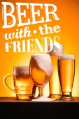 mugs of cold beer with froth on orange background with beer with the friends inspiration