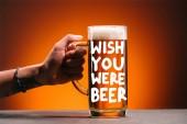 Fotografia ritagliata colpo della donna che tiene il vetro di birra fredda con schiuma su sfondo arancio con ispirazione wish che you were birra